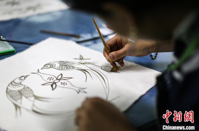 一名搬迁民众在进行传统蜡染绘画比赛。 黄晓海 摄