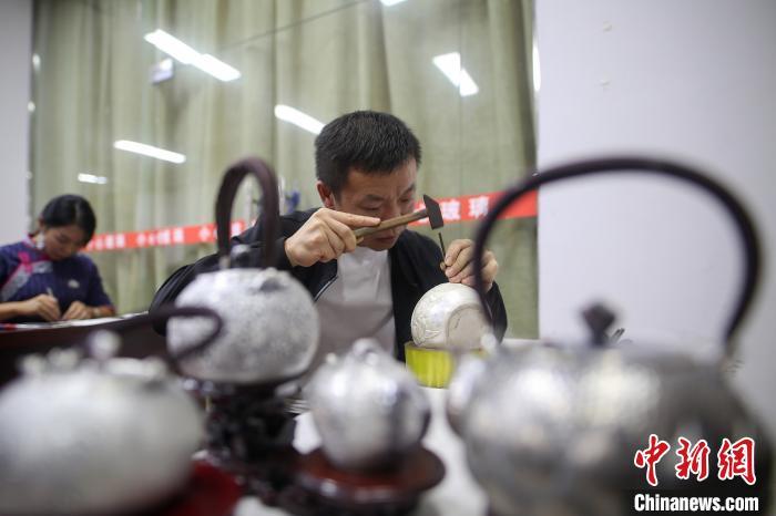 一名搬迁民众在进行传统银饰打制比赛。 黄晓海 摄