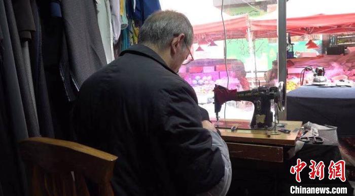 图为张怀友坐在缝纫机前修改服装。 蒲文思 摄