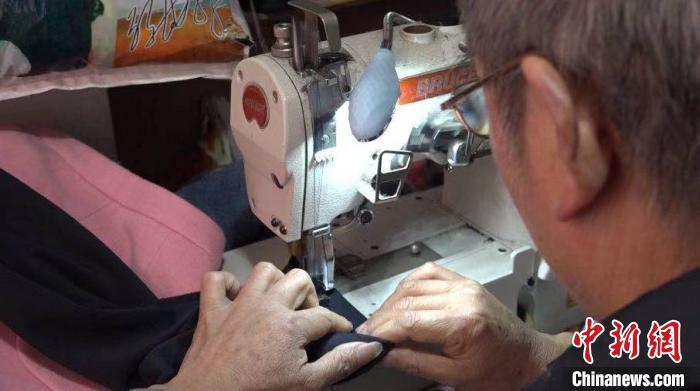 图为张怀友在使用电动缝纫机缝补。 蒲文思 摄